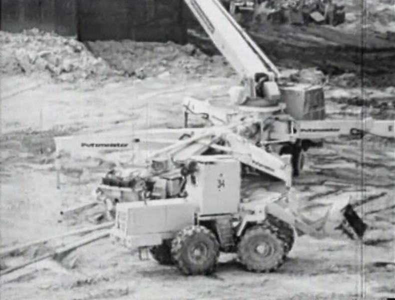 Модификация трактора Т-150 (на переднем плане), на заднем плане- бетононасос с дополнительной защитой кабины